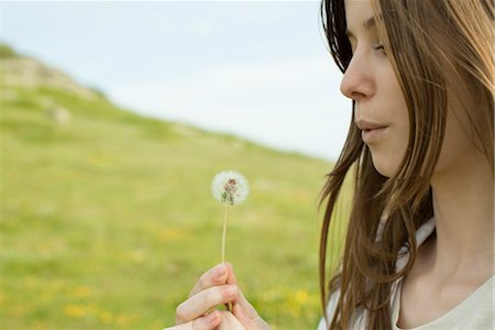 Young woman blowing on dandelion clock Stock Photo - Premium Royalty-Free, Code: 633-05401928