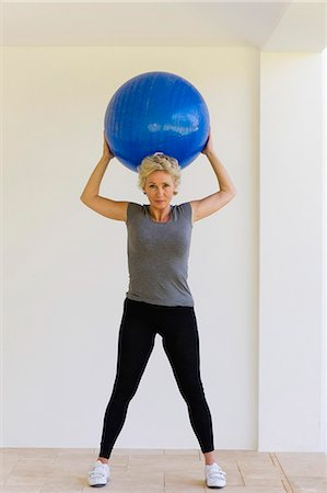 Mature woman holding up fitness ball behind head Stock Photo - Premium Royalty-Free, Code: 633-06322293