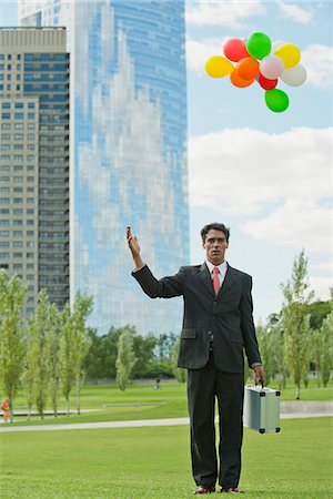 release - Businessman releasing bunch of balloons into air, looking disappointed Stock Photo - Premium Royalty-Free, Code: 633-06322425