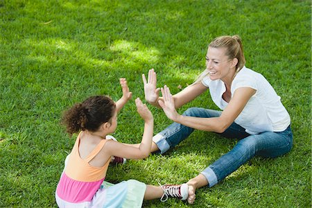 family shoes - Mother and daughter sitting on grass playing patty-cake Stock Photo - Premium Royalty-Free, Code: 633-06322572