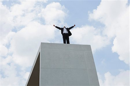 Businessman standing on concrete structure with arms outstretched, low angle view Stock Photo - Premium Royalty-Free, Code: 633-06322623