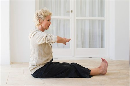 Mature woman practicing yoga on floor Stock Photo - Premium Royalty-Free, Code: 633-06354650