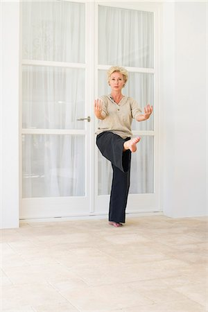 Mature woman balancing on one leg while exercising Stock Photo - Premium Royalty-Free, Code: 633-06354830