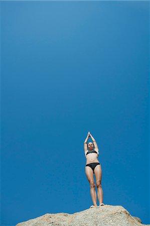 Girl in bikini standing against blue sky preparing to dive Stock Photo - Premium Royalty-Free, Code: 633-06354938