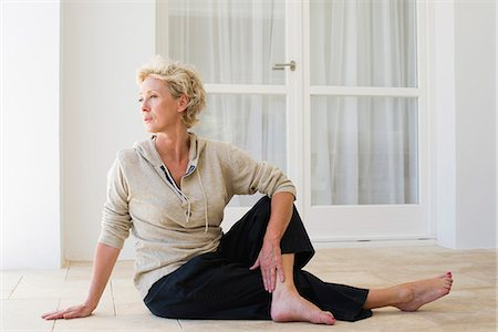 Mature woman sitting on floor doing spinal twist Stock Photo - Premium Royalty-Free, Code: 633-06354945
