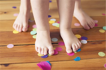 Barefeet and confetti on hardwood floor Stock Photo - Premium Royalty-Free, Code: 633-08150976