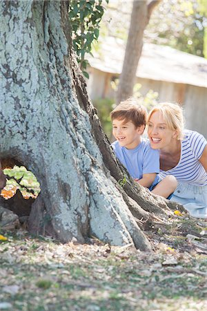 Young boy and mother hiding behind tree, playing hide-and-seek Stock Photo - Premium Royalty-Free, Code: 633-08151095
