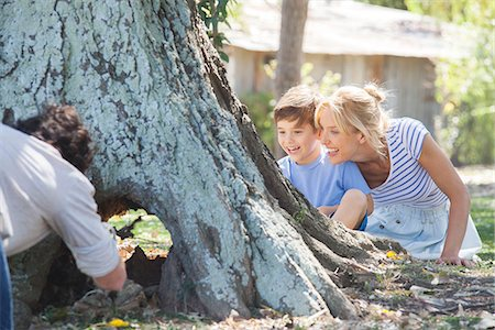 Young family exploring hollowed out tree trunk Stock Photo - Premium Royalty-Free, Code: 633-08151097