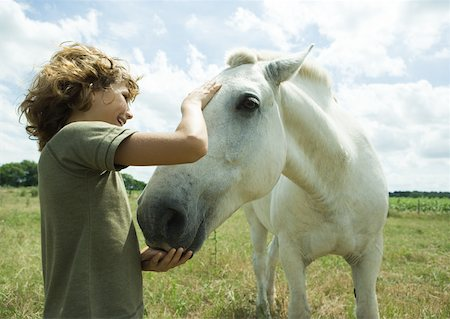 Boy petting horse Stock Photo - Premium Royalty-Free, Code: 633-01274774