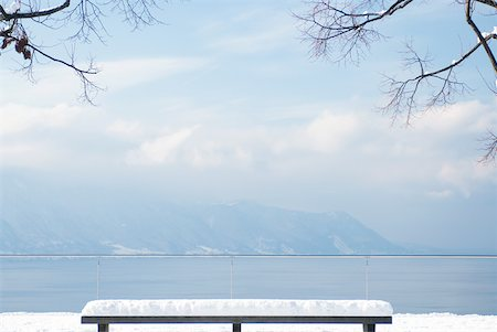 panoramic winter scene - Snow-covered bench overlooking lake and mountains Stock Photo - Premium Royalty-Free, Code: 633-01574004