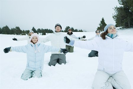 Group kneeling in snow with arms out and eyes closed Stock Photo - Premium Royalty-Free, Code: 633-01574548