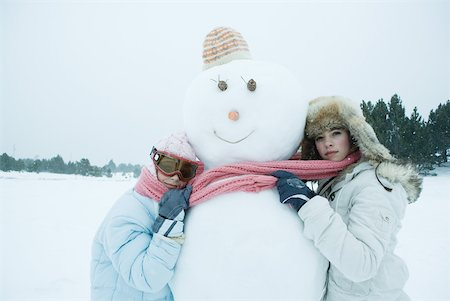 Two friends hugging snowman Stock Photo - Premium Royalty-Free, Code: 633-01574562