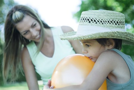 Mother and son, boy blowing up balloon while mother watches Stock Photo - Premium Royalty-Free, Code: 633-01714799