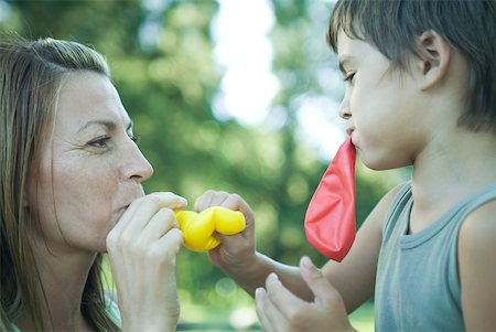 Boy and mother blowing up balloons Stock Photo - Premium Royalty-Free, Code: 633-01714802