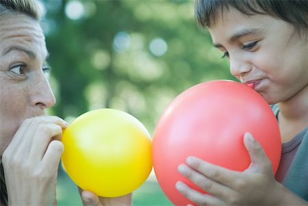 Boy and mother blowing up balloons Stock Photo - Premium Royalty-Free, Code: 633-01714803