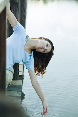 Woman leaning off edge of dock, dangling hand toward water Stock Photo - Premium Royalty-Free, Code: 633-01715366