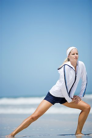 Young woman on beach, stretching Stock Photo - Premium Royalty-Free, Code: 633-01715677