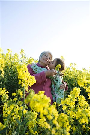 preteen kissing - Girl kissing grandmother on cheek, standing in field of yellow flowers Stock Photo - Premium Royalty-Free, Code: 633-01715825