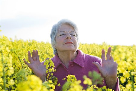 Senior woman standing in field of canola, eyes closed, hands up Stock Photo - Premium Royalty-Free, Code: 633-01715839