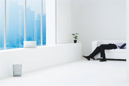 Businessman lying on sofa in minimalist high rise apartment, cropped view Stock Photo - Premium Royalty-Free, Code: 633-01837166