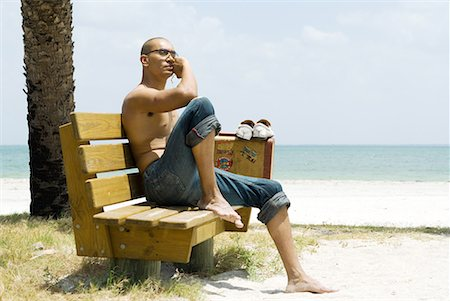 Man at the beach, sitting on bench beside suitcase, looking away Stock Photo - Premium Royalty-Free, Code: 633-02044611