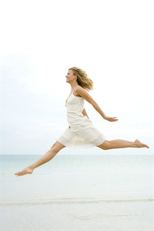 forward - Woman jumping in the air at the beach, side view Stock Photo - Premium Royalty-Free, Code: 633-02065824