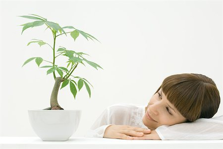 silk floss tree - Woman contemplating plant, resting head on arm Stock Photo - Premium Royalty-Free, Code: 633-02128708