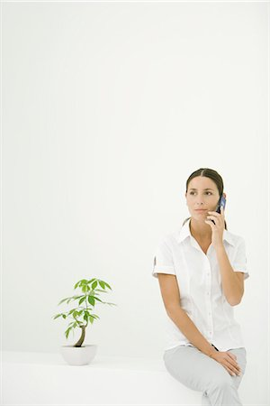 silk floss tree - Woman sitting beside potted plant, using cell phone Stock Photo - Premium Royalty-Free, Code: 633-02128797