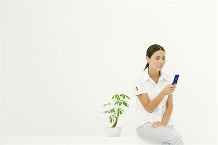 silk floss tree - Woman sitting beside potted plant, using cell phone Stock Photo - Premium Royalty-Free, Code: 633-02231700