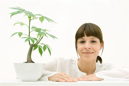 silk floss tree - Woman sitting with potted plant, smiling at camera Stock Photo - Premium Royalty-Free, Code: 633-02231755