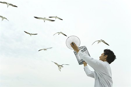 release - Man holding up bird cage, releasing bird, gulls souring overhead Stock Photo - Premium Royalty-Free, Code: 633-02417909
