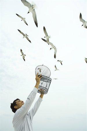 release - Man holding up emZSy birdcage, birds flying overhead Stock Photo - Premium Royalty-Free, Code: 633-02417916