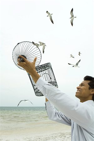 release - Man releasing bird at the beach, emZSy bird cage in hands Stock Photo - Premium Royalty-Free, Code: 633-02417926