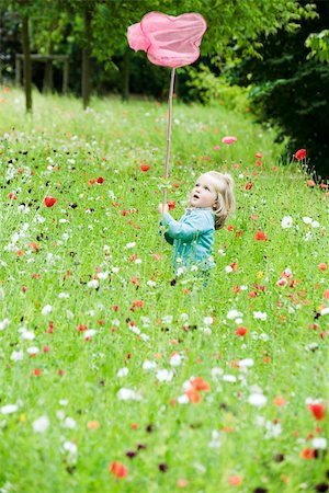 Little girl holding up butterfly net, standing in field of flowers Stock Photo - Premium Royalty-Free, Code: 633-02417965