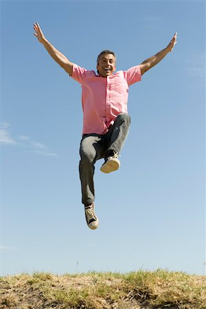 dynamic - Excited man jumping into the air with arms raised Stock Photo - Premium Royalty-Free, Code: 633-03194699