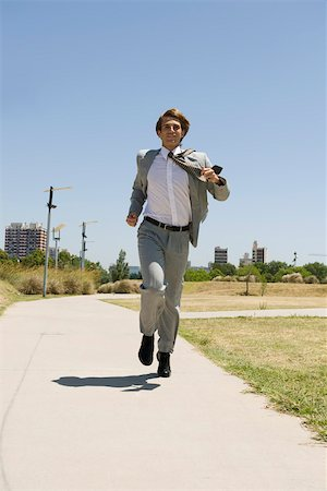 dynamic - Businessman running down sidewalk with look of happiness Stock Photo - Premium Royalty-Free, Code: 633-03194788