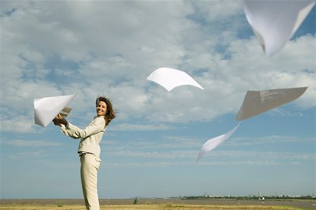 release - Woman outdoors tossing document into air watching pages caught by wind fly away Stock Photo - Premium Royalty-Free, Code: 633-03194815