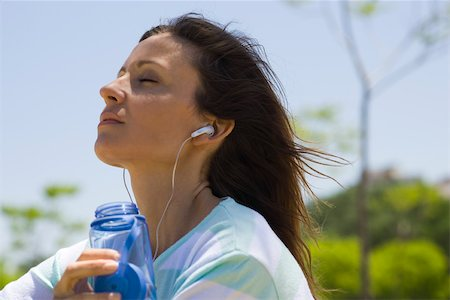 Woman listening to earphones outdoors Stock Photo - Premium Royalty-Free, Code: 633-03444664