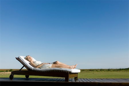 Woman napping on lounge chair on deck Stock Photo - Premium Royalty-Free, Code: 633-03444733