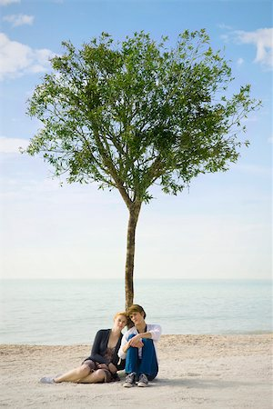 sitting under tree - Young couple sitting together beneath tree on beach Stock Photo - Premium Royalty-Free, Code: 633-03444996