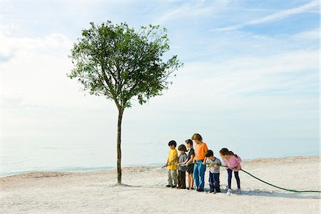 Ecology conceZS, children watering tree growing on beach Stock Photo - Premium Royalty-Free, Code: 633-03444999
