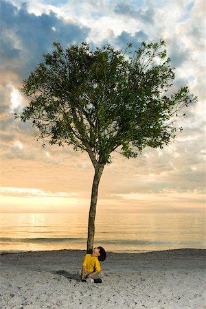 sitting under tree - Boy sitting beneath tree on beach Stock Photo - Premium Royalty-Free, Code: 633-03445009
