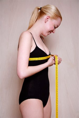 Woman measuring her chest Stock Photo - Premium Royalty-Free, Code: 644-01435997