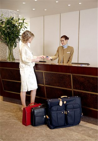 Woman checking in at the hotel reception desk Stock Photo - Premium Royalty-Free, Code: 644-01436200
