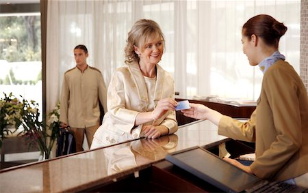 Woman checking in at the hotel reception desk Stock Photo - Premium Royalty-Free, Code: 644-01436201