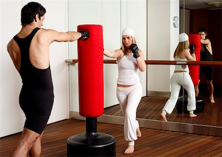 student fighting - Young man and woman hitting the punching bag Stock Photo - Premium Royalty-Free, Code: 644-01436528