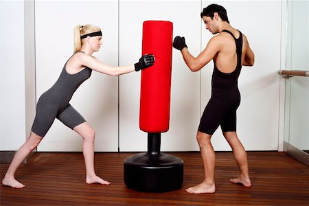 student fighting - Young man and woman practicing with a punching bag Stock Photo - Premium Royalty-Free, Code: 644-01436970