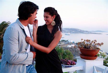 Couple eating grapes on balcony Stock Photo - Premium Royalty-Free, Code: 644-01437303