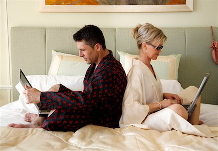 Mature couple working in bed Stock Photo - Premium Royalty-Free, Code: 644-01437318
