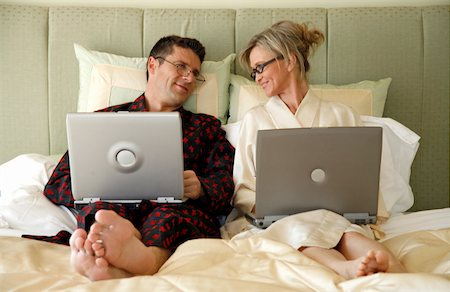 Mature couple working in bed Stock Photo - Premium Royalty-Free, Code: 644-01437319